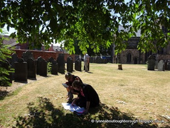 Visitors research the tombstones